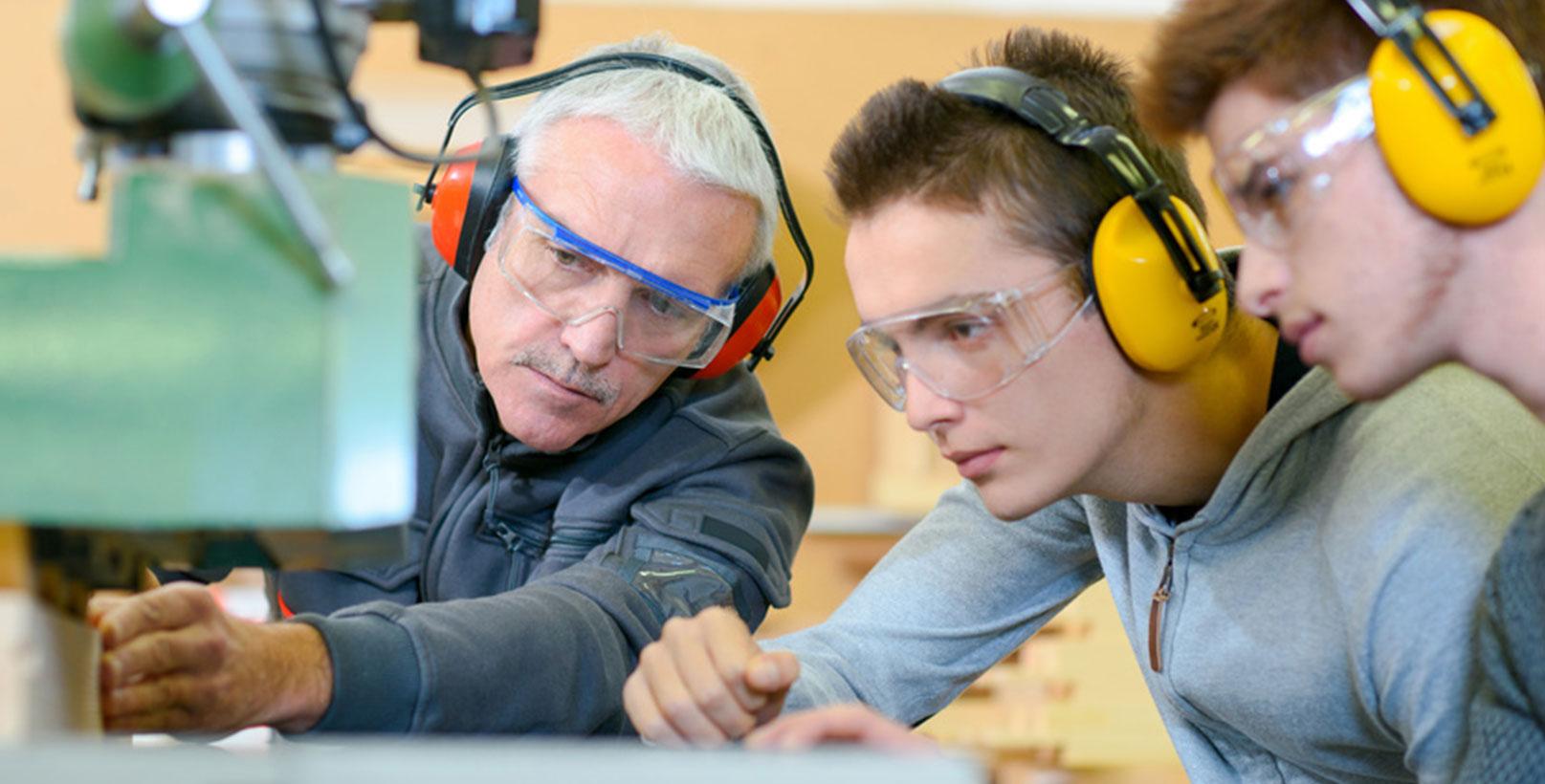 Zwei Auszubildende und Meister analysieren Maschine