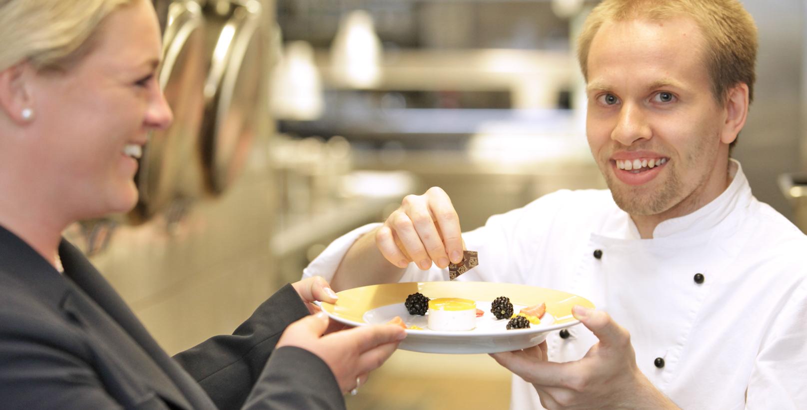 Auszubildener einer Koch-Ausbildung bei der Zubereitung eines Desserts